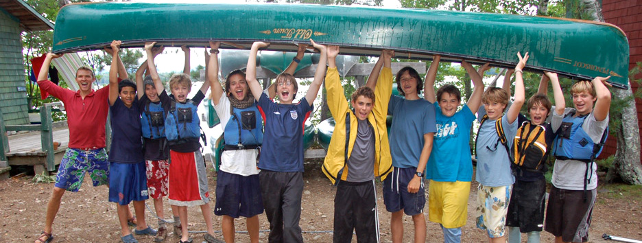 Campers on Pine Island hold up a canoe.